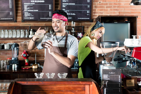 Photo pour Woman and man in Asian cafe preparing coffee and smelling on fresh coffee beans - image libre de droit
