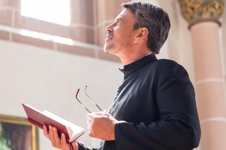 Photo pour Catholic priest reading bible in church - image libre de droit