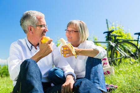 Foto de Senior couple eating fruit and drinking at picnic in summer, beautiful landscape in the background - Imagen libre de derechos