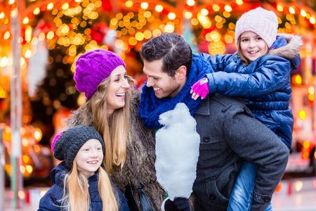 Photo pour Family eating cotton candy on Christmas market - image libre de droit