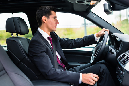 Photo for Man driving his car for business travel wearing a suit - Royalty Free Image