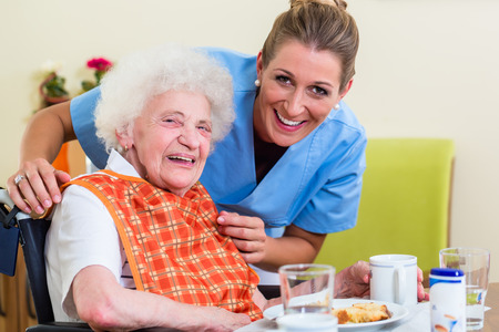 Photo pour Nurse with senior woman helping with meal - image libre de droit