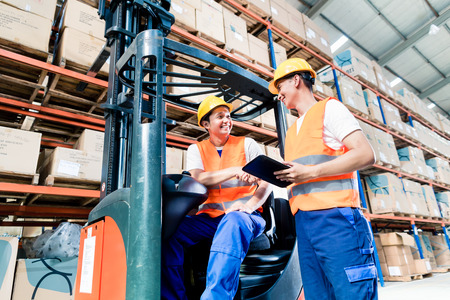 Photo pour Workers in logistics warehouse at forklift checking list - image libre de droit