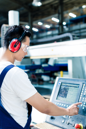 Photo for Worker entering data in CNC machine at factory floor to get the production going - Royalty Free Image