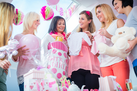 Foto de Expecting Mother with presents on baby shower party getting a romper suit, her friends sitting on couch - Imagen libre de derechos