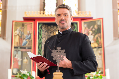Photo for Priest in church with bible in front of altar - Royalty Free Image