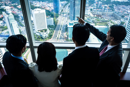 Photo pour Group of Asian real estate business people looking at city skyline from skyscraper office building - image libre de droit