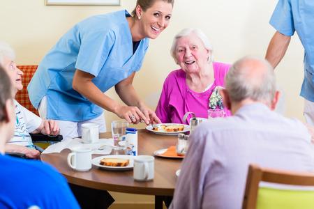 Foto de Group of seniors having food in nursing home, a nurse is serving - Imagen libre de derechos
