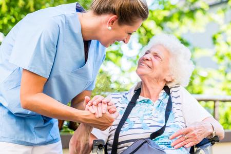 Foto de Nurse holding hand of senior woman in pension home - Imagen libre de derechos