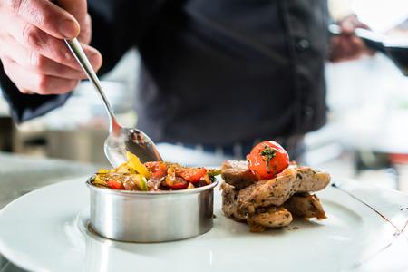 Foto für Chef finishing food on plate in restaurant or hotel kitchen  - Lizenzfreies Bild