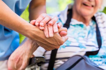 Photo pour Nurse consoling senior woman holding her hand - image libre de droit