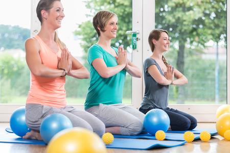 Photo pour Young women doing  yoga during postnatal recovery lesson - image libre de droit