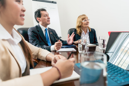 Male and female senior managers sitting down during an important interactive meeting in the conference room of a successful corporation