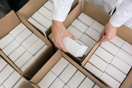 Foto de High-angle close-up view of the hands of a manufacturing worker putting packed products, in cardboard boxes before export or shipping during manual work in a cosmetics factory - Imagen libre de derechos