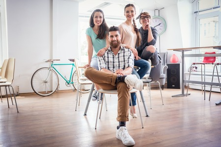Foto de Portrait of four co-workers smiling and looking at camera while wearing cool casual clothes, during work in the shared office space of a modern hub for freelancers and young entrepreneurs - Imagen libre de derechos
