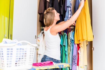 Young woman putting shirt after laundry back into wardrobe
