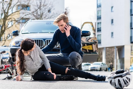 Photo pour Full length view of a worried young driver calling the ambulance after hitting and injuring accidentally a female bicyclist on a city street - image libre de droit