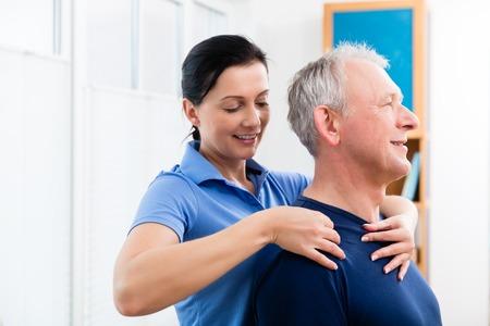 Masseuse applying neck massage on older man