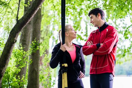 Couple having break from sling training