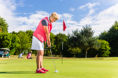 Photo pour Senior golf playing woman putting on green - image libre de droit