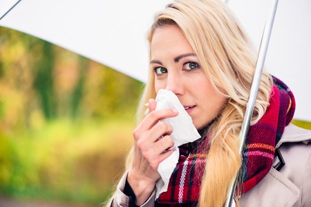 Woman having cold or flu due to bad autumn or fall weather