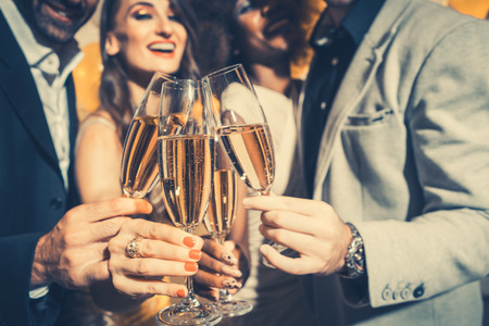 Foto de Men and women celebrating birthday or new years party while clinking glasses with sparkling wine - Imagen libre de derechos