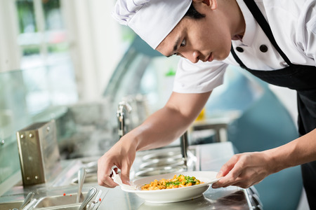 Photo pour Gourmet chef plating up a dish of food in an Asian restaurant carefully wiping the sides of the plate for spillage - image libre de droit