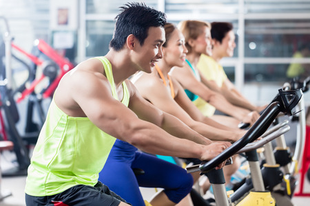 Photo for Group of young Asian athletes side by side during spinning class workout - Royalty Free Image
