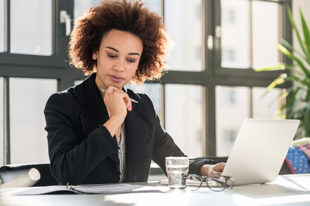 Foto de Portrait of African American female expert analyzing printed business report while sitting at desk in the office - Imagen libre de derechos