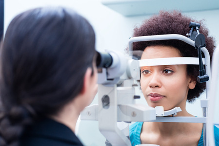 Foto de Optician measuring women eyes with refractometer in optician shop - Imagen libre de derechos