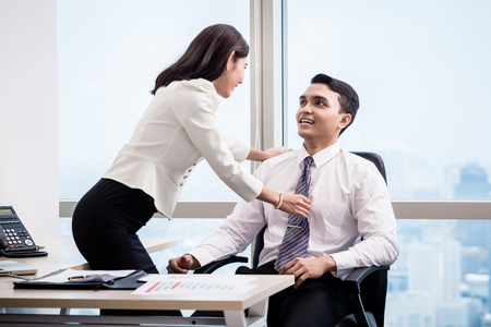 Asian business man and woman flirting in the office having workplace affair