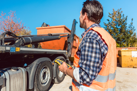 Photo pour Worker on construction site unloading container for waste from truck using remote control - image libre de droit