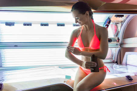 Beautiful fit woman smiling while applying nutritive oil on her skin before indoor tanning in a modern beauty salon