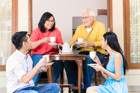 Foto de Side view of young man and woman visiting parents at home in the afternoon at tea time - Imagen libre de derechos