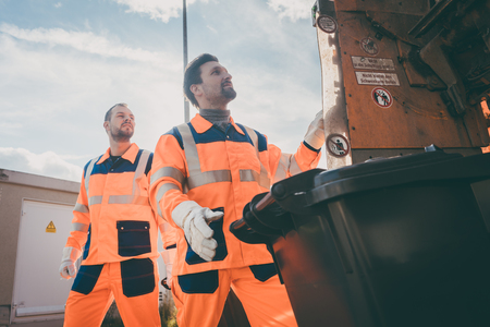 Photo pour Two garbagemen working together on emptying dustbins for trash removal - image libre de droit