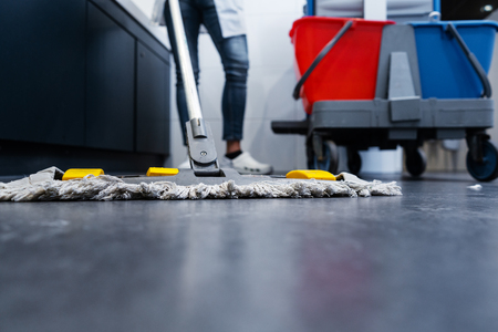 Photo for Low shot of cleaning lady mopping the floor in restroom beside her trolley - Royalty Free Image