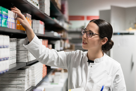 Foto de Portrait of a dedicated female pharmacist taking a medicine from the shelf, while wearing eyeglasses and lab coat during work in a modern drugstore with various pharmaceutical products - Imagen libre de derechos
