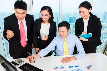 Group of successful businesspeople looking at computer with graph chart on the deskの写真素材