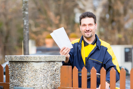 Postman delivering letters to mailbox of the recipient