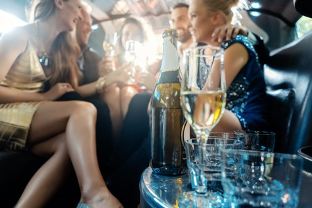 Photo pour Women and men celebrating with drinks in a limousine car, focus on the alcohol bottle - image libre de droit