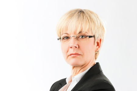 Photo for Portrait of a bossy senior woman wearing spectacles and black coat isolated against while background looking at camera - Royalty Free Image