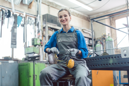 Female mechanic sitting in metal workshop looking and smiling into camera