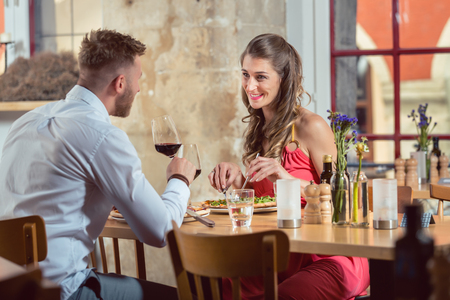 Photo for Happy young couple eating food with red wine at restaurant - Royalty Free Image