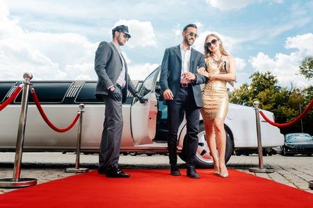 Photo pour Couple arriving with limousine walking red carpet, a driver is opening the car door - image libre de droit