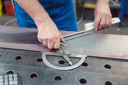 Metalworker using folding rule to measure steel strip for later cutting