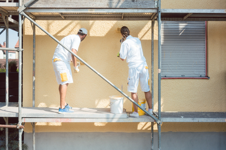 Photo pour Back view of man and woman painter working coloring wall yellow - image libre de droit
