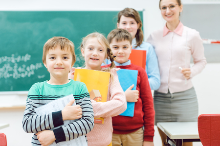 Photo for Proud students with books and teacher standing in school class - Royalty Free Image