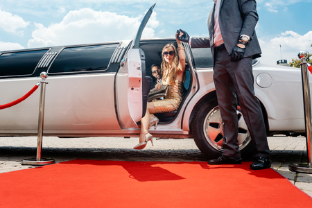 Photo pour Driver helping VIP woman or star out of limo on red carpet to a reception - image libre de droit