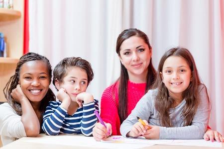Photo pour Portrait of smiling woman sitting with children doing drawing on table - image libre de droit