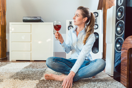 Photo pour Woman having glass of wine in front of Hi-Fi speakers enjoying the drink and the music - image libre de droit